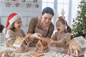 Mother and two daughters decorate gingerbread houses