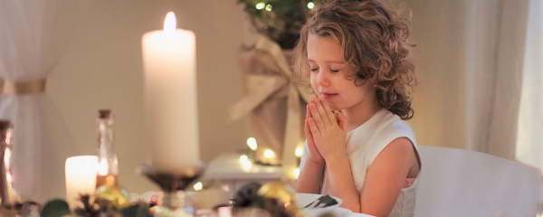 A young girl prays before Christmas dinner.
